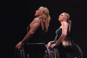 Two women who use wheelchairs are dancing in a modern dance performance.