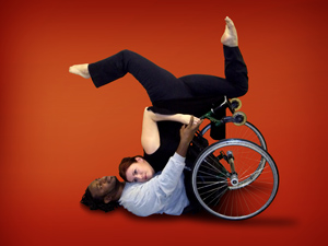 A man that uses a wheelchair is dancing with a woman in a modern dance pose.
