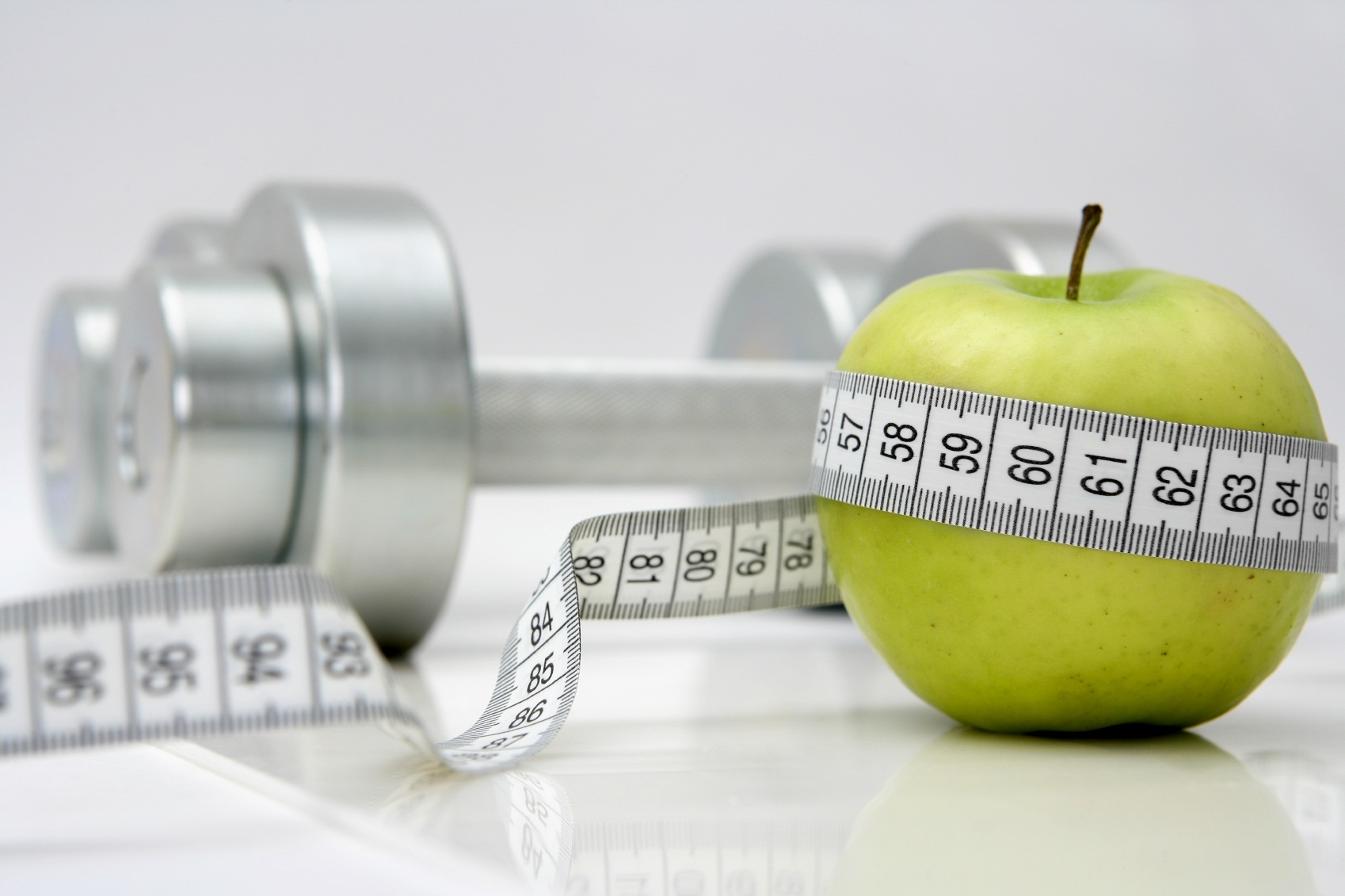 A picture of measuring tape, an apple, and a pair of dumbbells