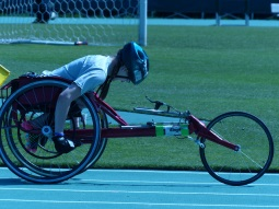 a participant uses a racing chair in a track event