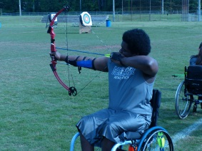 a participant competes in an archery event, shooting from a wheelchair