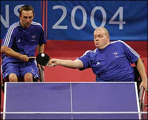 a team of ping pong players compete from wheelchairs