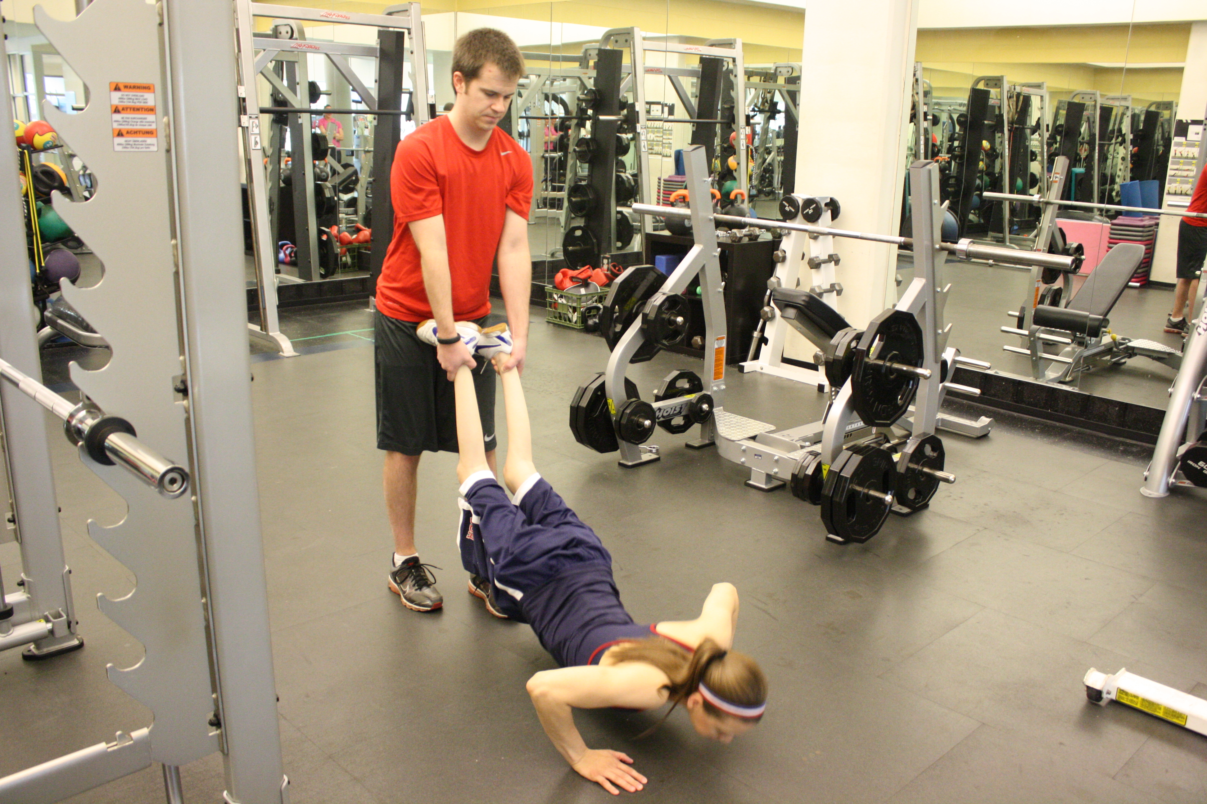 trainer assists client with pushups