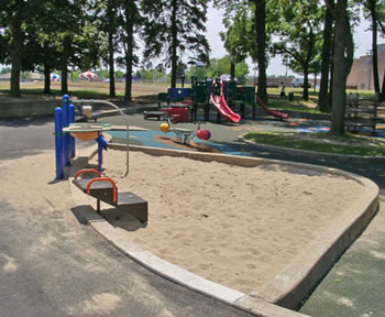 This sand play area offers a sand table, a transfer system, and concrete containment edging that users may sit on.