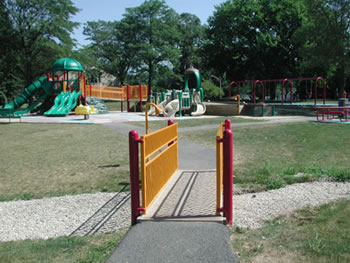 At this playground, the safety barriers are yellow, the play equipment for children 2 to 5 years old is tan with green accents, and the play equipment for children 5 to 12 years old is green.