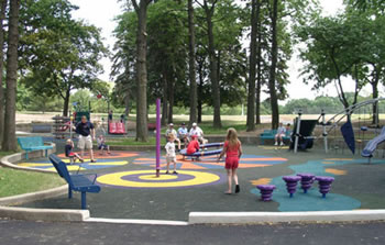 Four spinning pieces of equipment are dispersed on this playground. The 4- to 6-foot use zone around each piece of equipment is colorfully designed with stripped and swirling circles on the unitary rubber ground surface.