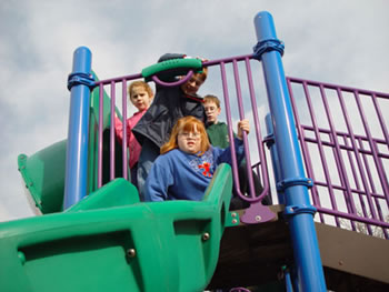A girl sits to enter a slide on an elevated platform while surrounded by three friends.