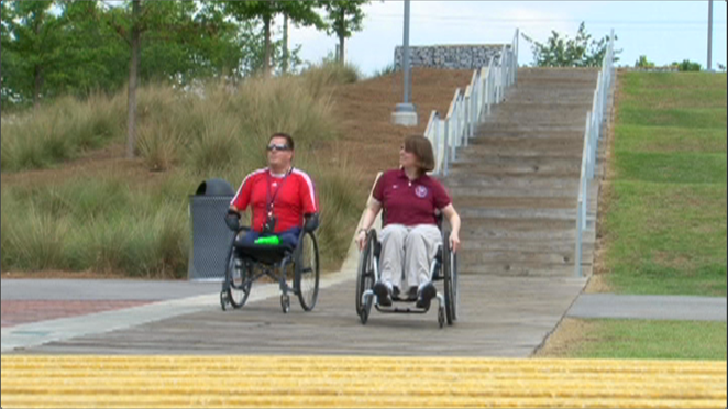 two wheelchair users pushing at a park