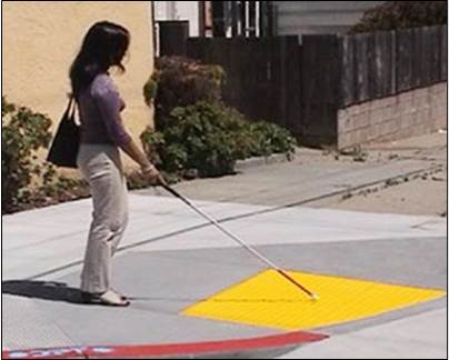 a woman with a walking cane for visual impairment feels truncated domes on a curb cut ramp