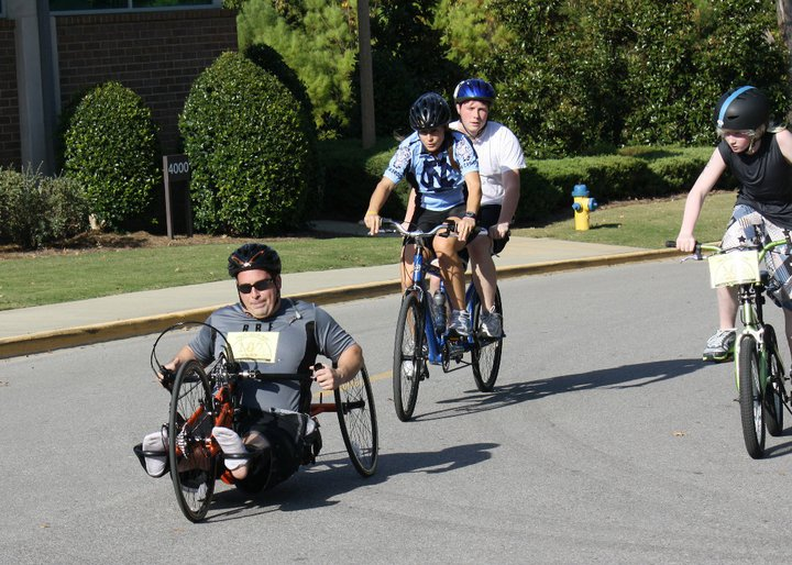 a group of individuals ride together on a bicycle, handcycle, and tandem bicycle