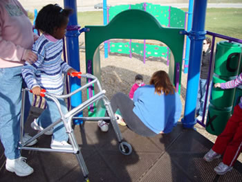 A child using a walker waits on the elevated platform for her turn to go down the slide.