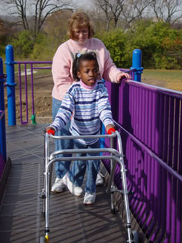 A child using a walker moves up the elevated ramp platform with assistance from an adult caregiver.