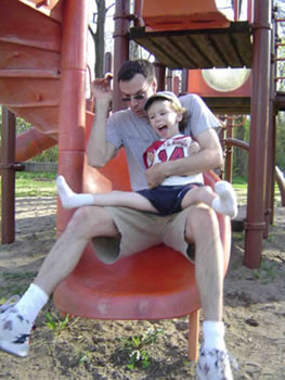 A father descends a spiral slide with his son on his lap.