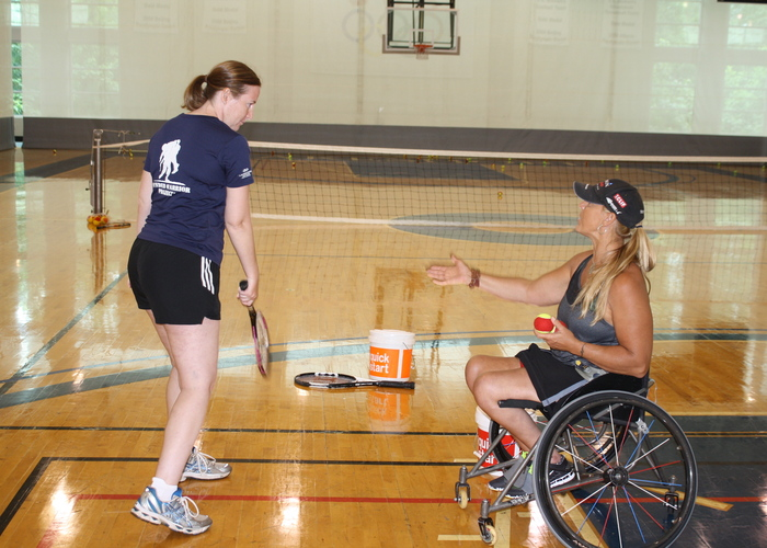 wheelchair tennis player teaching a standing player
