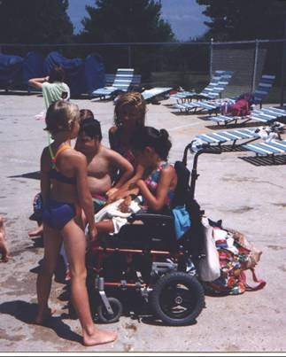 A girl in her wheelchair surrounded by family at the pool.