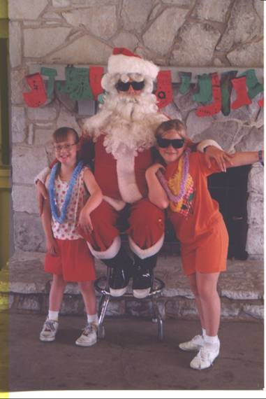 Two girls posing with Santa Clause in front of a fireplace.
