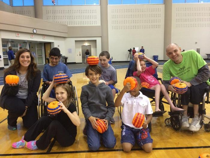 a group of children and staff hold pumpkins for bocce