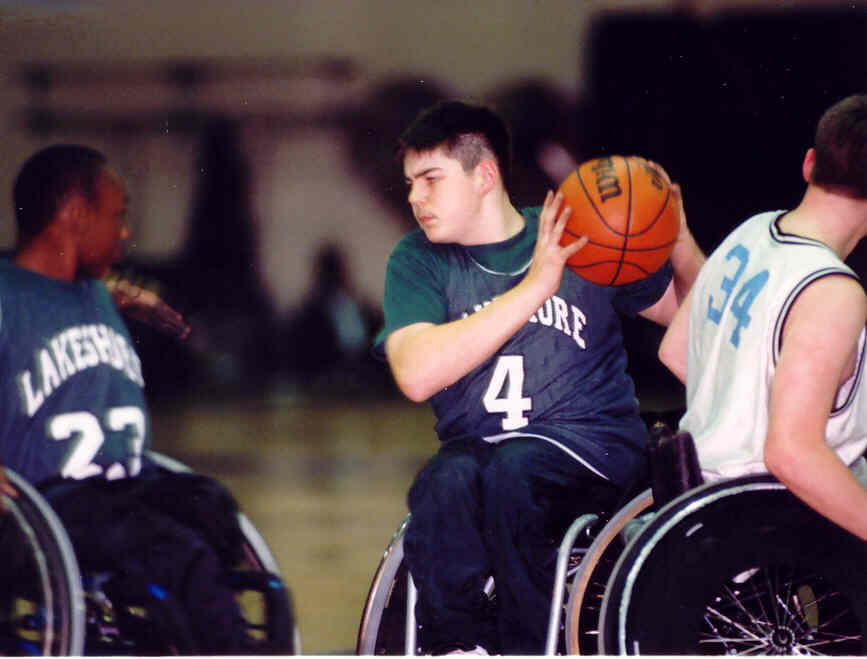 three young men play wheelchair basketball