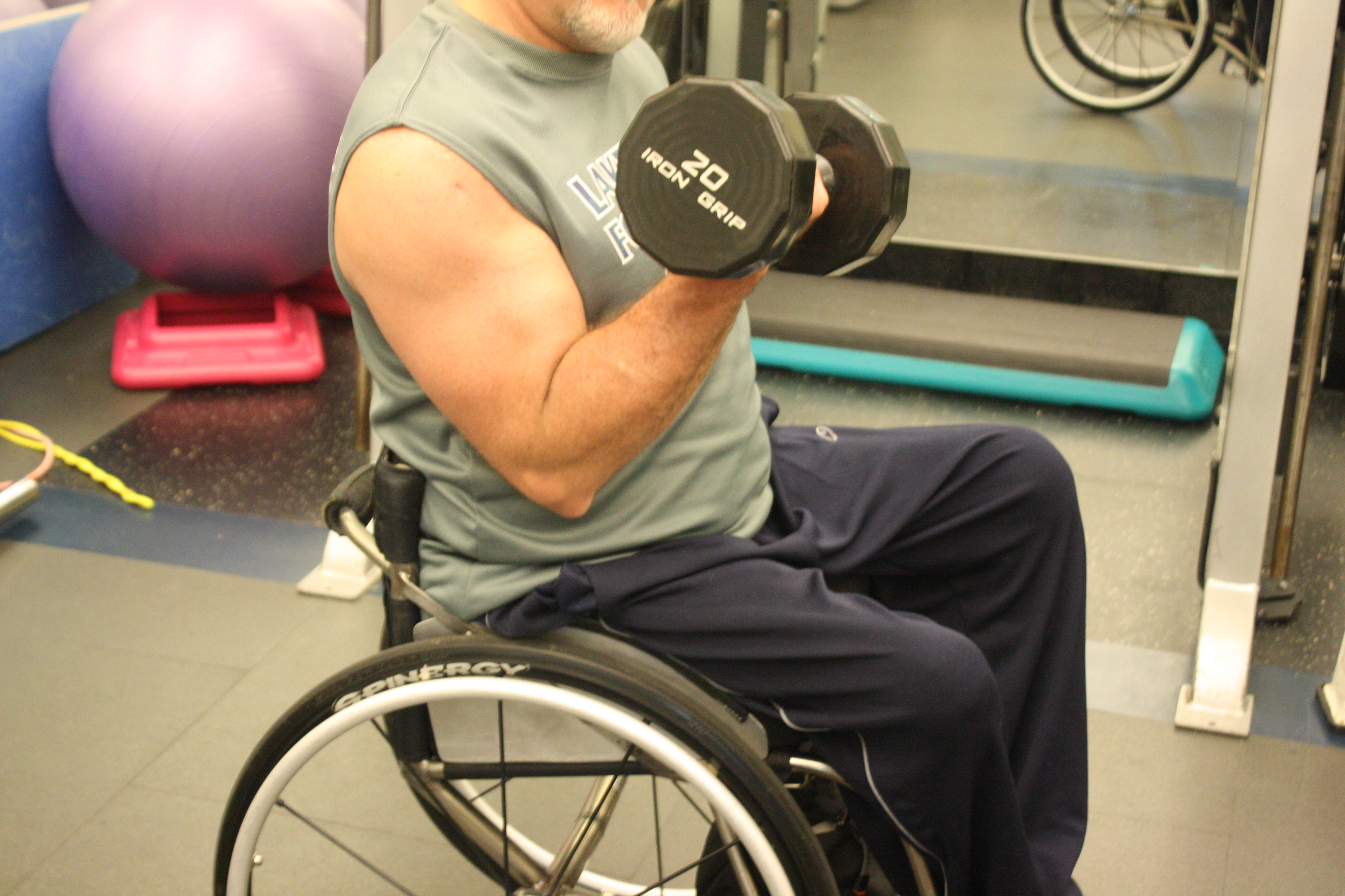 man in wheelchair doing biceps curl