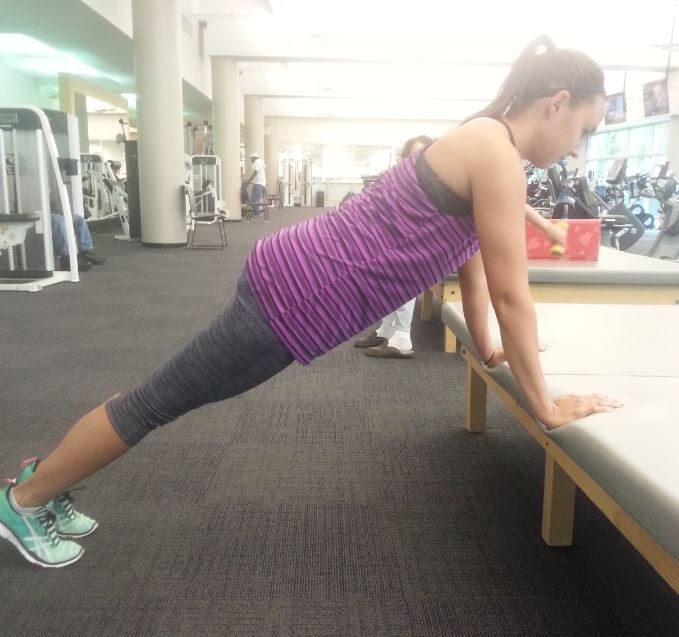 girl does easier plank with assistance of elevated bench