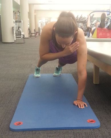 girl performs plank with shoulder taps