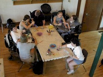 Top view of a large  square wooden  table surrounded by three people using wheelchairs painting with four people without disabilities