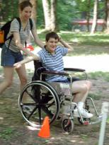 Photo of a young man using a wheelchair being pushed through and obstacle course.