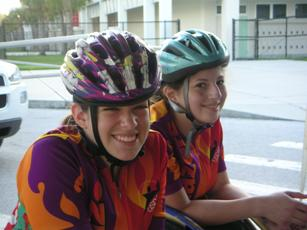Two girls who use wheelchairs are dressed in colorful cycling shirts and helmets as they smile at the camera.