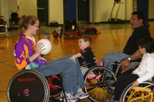 Image of wheelchair users of various ages playing wheelchair basketball