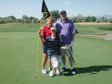 Mother, father, and son standing on a golf course.
