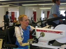 Image of a woman with right arm prosthesis using an arm ergometer