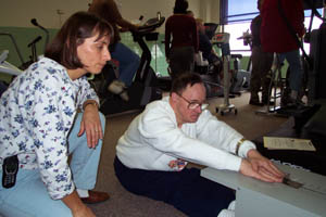 Picture of a personal trainer working with a  person with a disability in a fitness center.