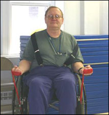 A man seated in a wheelchair is demonstrating the start position for a  biceps curl exercise using a theraband