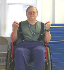A man seated in a wheelchair is demonstrating the end position for a biceps curl exercise using a theraband