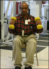 A man is seated demonstrating the end position for a Hammer Bicep Curl with Free Weights exercise