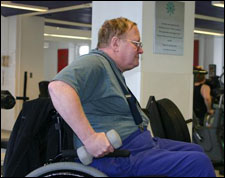 A man seated a wheelchair is demonstrating the start position for a Double Arm Triceps Kickback with Free Weights exercise