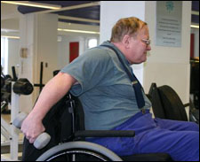 A man seated in a wheelchair is demonstrating the end position for a Double Arm Triceps Kickback with Free Weights exercise