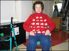 A woman seated in a wheelchair is demonstrating the start position for a Upright Row with Free Weights exercise
