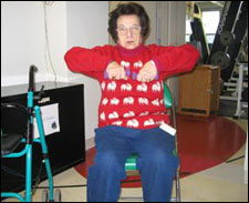A woman seated in a wheelchair is demonstrating the end position for a Upright Row with Free Weights exercise