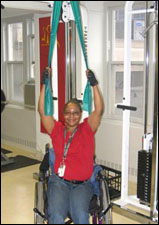 A woman is seated demonstrating a start position for a Lat Pull Down with Thera-Band® exercise