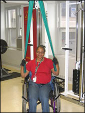 A woman is seated demonstrating an end position for a Lat Pull Down with Thera-Band® exercise