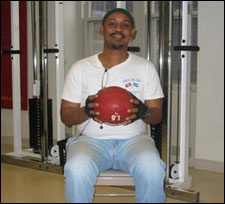 A man is seated demonstrating a start position for a Trunk Rotation Exercises with a Medicine Ball
