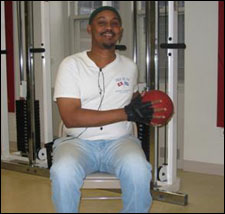A man is seated demonstrating an end position for a Trunk Rotation Exercises with a Medicine Ball