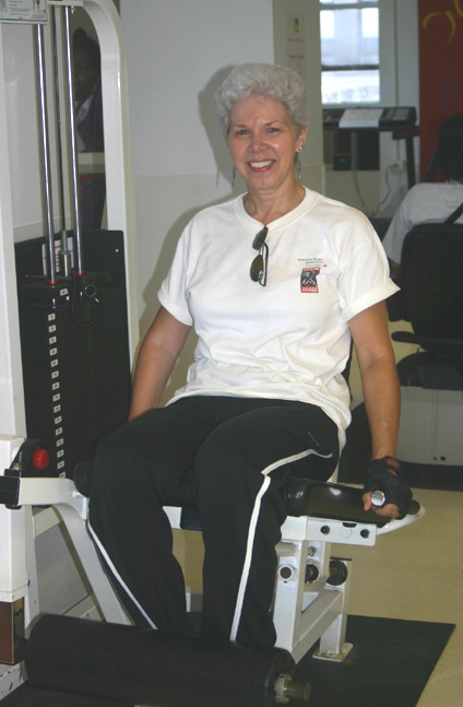 An adult woman is sitting on a Leg Extension exercise equipment