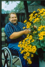Man using wheelchair pruning plants growing in planter at chest height