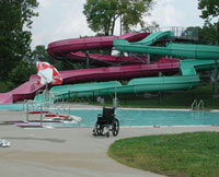 A wheelchair sits in front of a water slide at an aquatic facility.
