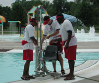 Three lifeguards stand near an outdoor pool inspecting the  pool lift.