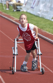 A young boy using a walker during a track and field event
