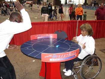 Two individuals (one using a wheelchair) play a game of Bulletball.