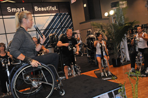 A women in a wheelchair is leading a group of people through an exercise class on an upper body cycle.